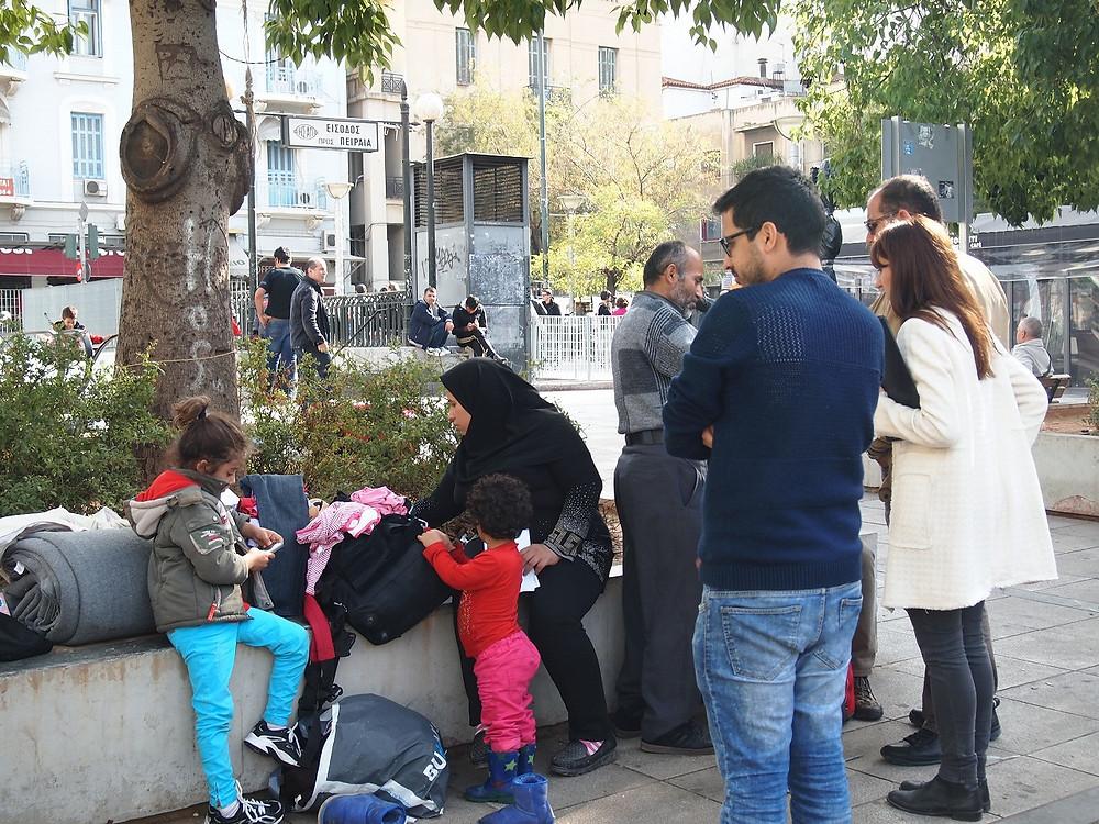 アテネ都心のヴィクトリア広場で支援団体と話す難民の家族