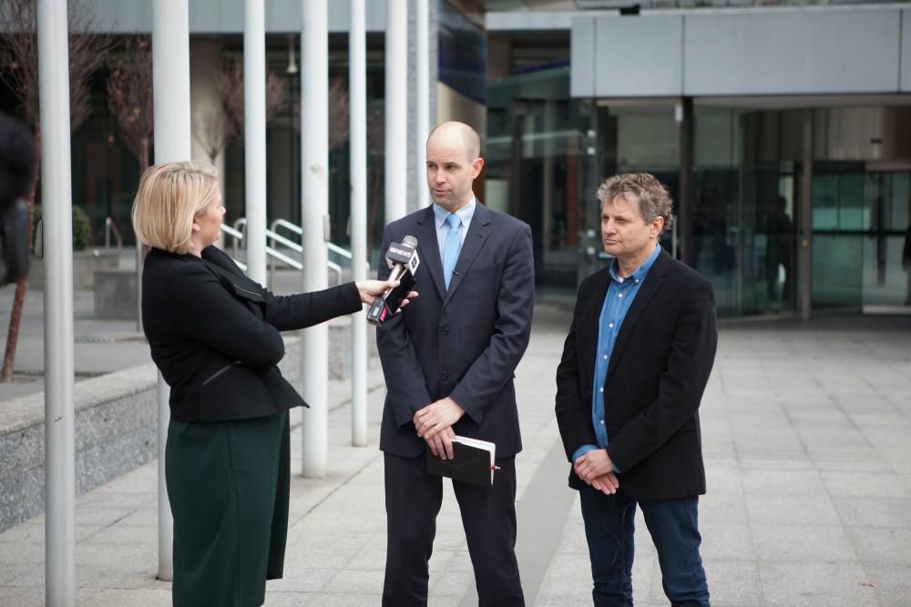 8月8日メルボルンにある、オーストラリア連邦裁判所の前で、ABC TVのエマ・ヤンガー記者(左)にインタビューを受けるバーンデン弁護士(中央)と原告のガイ・アブラハムスさん(右) © Cam Sutti