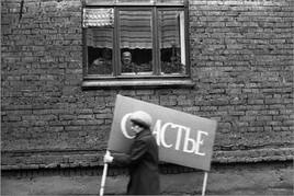 Носительница счастья, спешащая на демонстрацию. Улица Обнорского. Новокузнецк. 1.05.1983