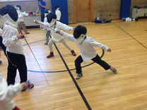 Beginning fencers practice the basics of fencing
