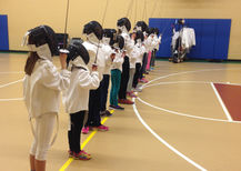 Children learn the fencing salute