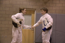 Two fencers shake hands after a fencing bout
