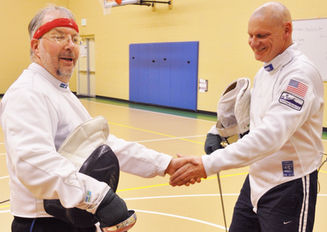 Two fencers shake hands after a bout