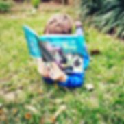 kid in garden reading Bug and Boo.jpg