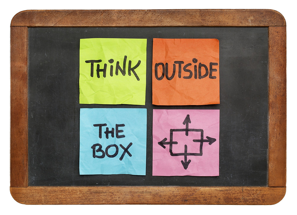 think outside the box concept - colorful sticky notes on a vintage slate blackbo