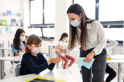 Teacher, children with face mask at scho