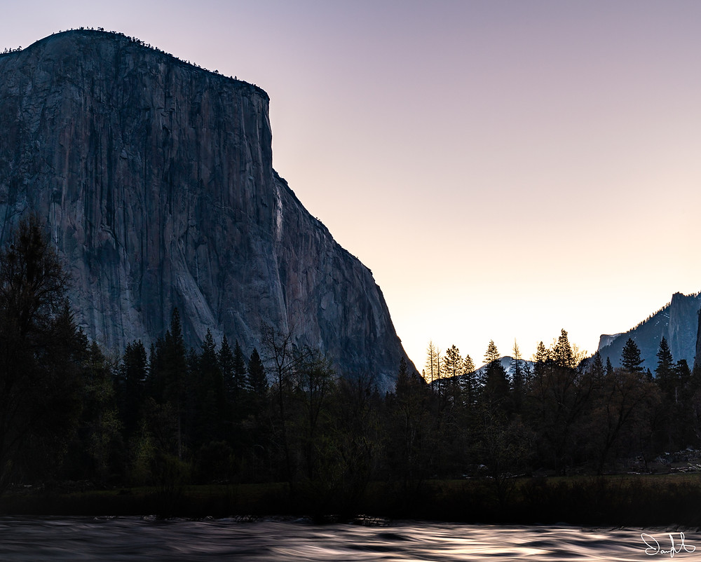 El Capitan is silhouetted against a purple sky at sunrise