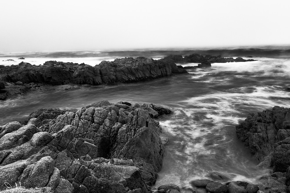 black and white with rocks and ocean