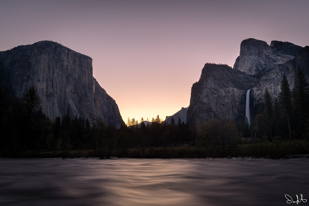 A purple sunrise illuminates the Gates of the Valley and the Merced River