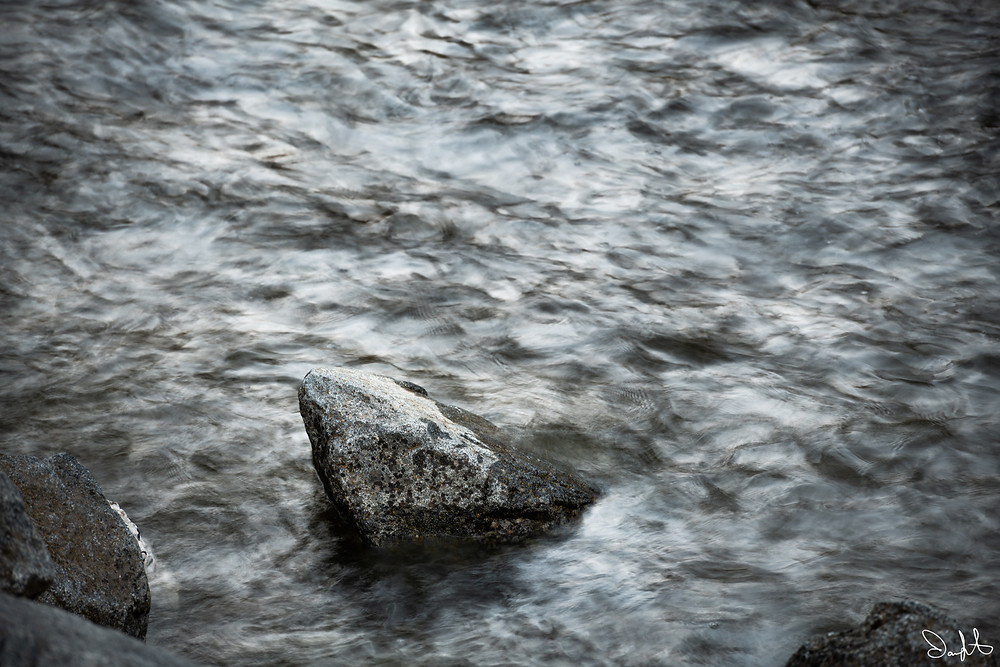 A boulder in the merced river during the spring flood
