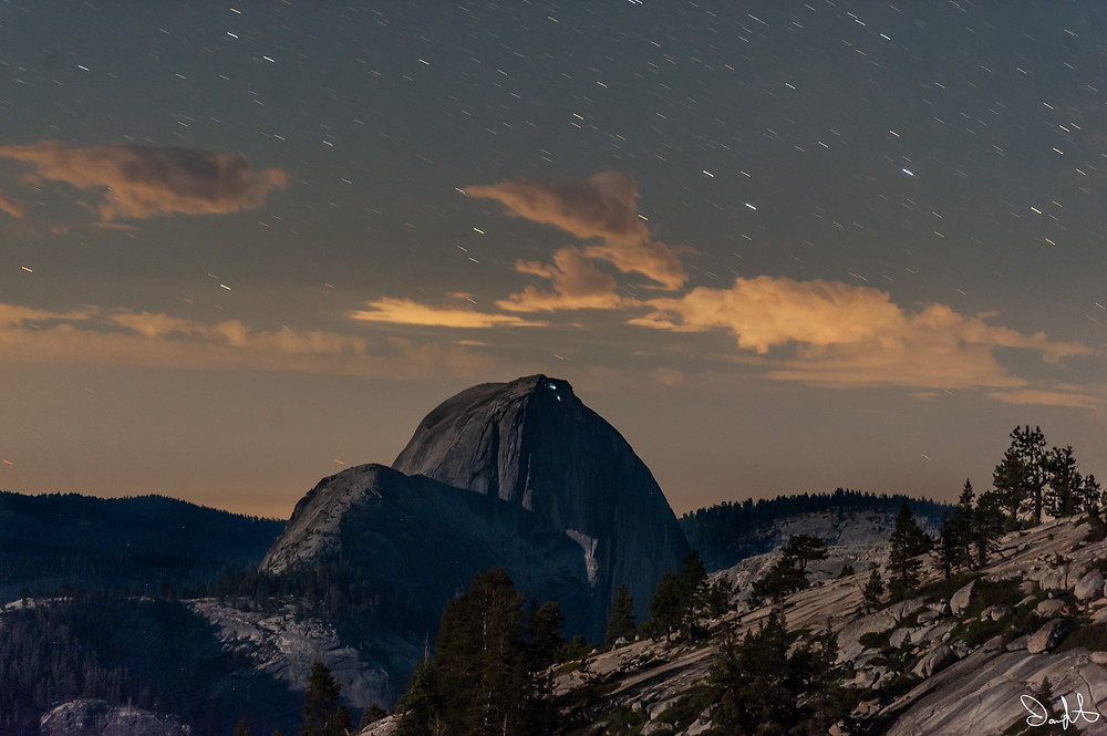 Stars streak across the sky behind Half Dome as climbers near the summit