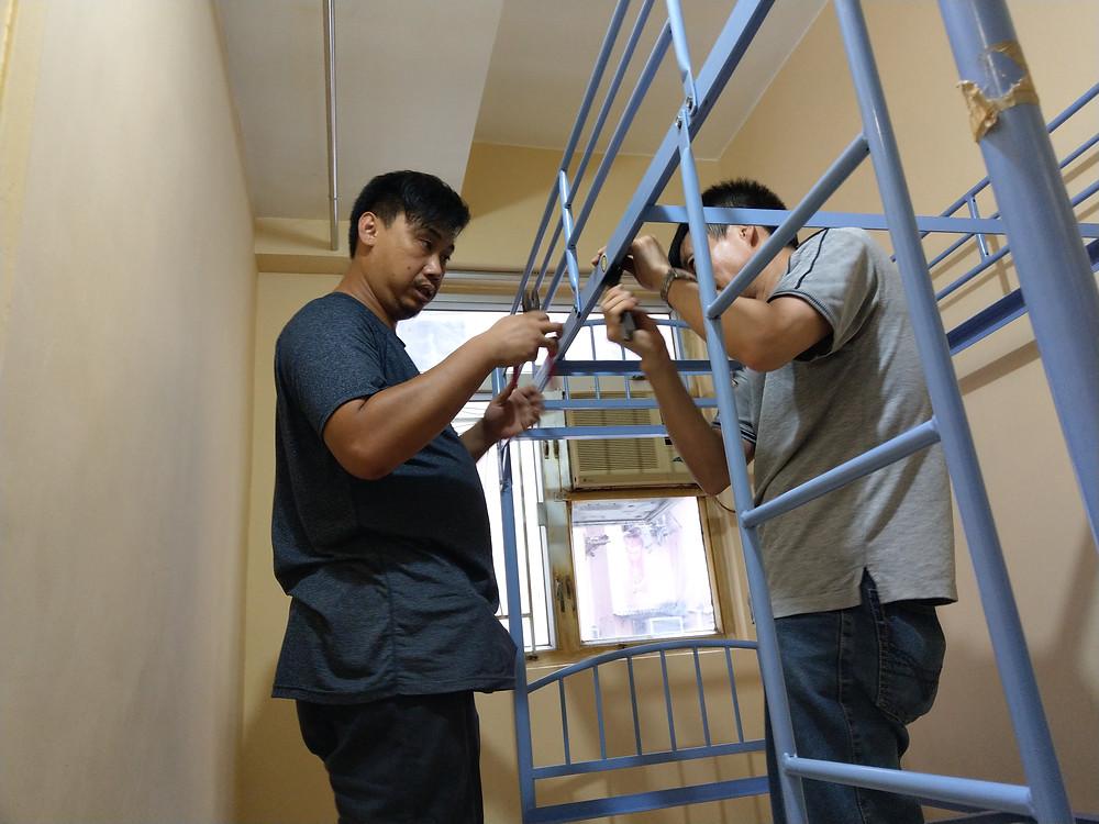 志工莊智聰 ( 左 ) 協助何先生組裝床架  攝影/梁昌材