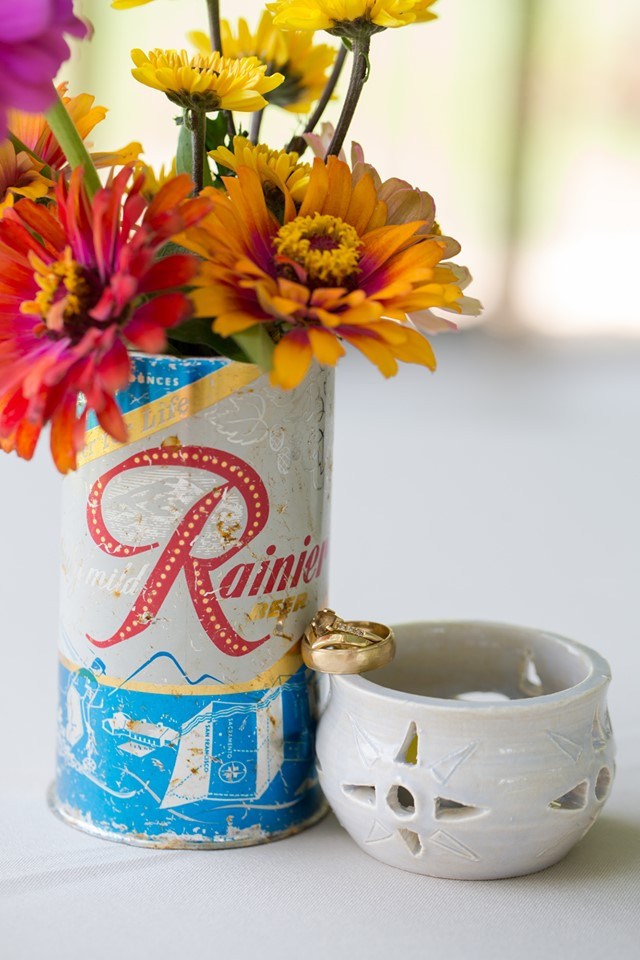 Gold wedding rings nestled in a DIY wedding centerpiece. The centerpiece has colorful zinnias inside a vintage Rainier Beer can, next to a handmade ceramic votive.