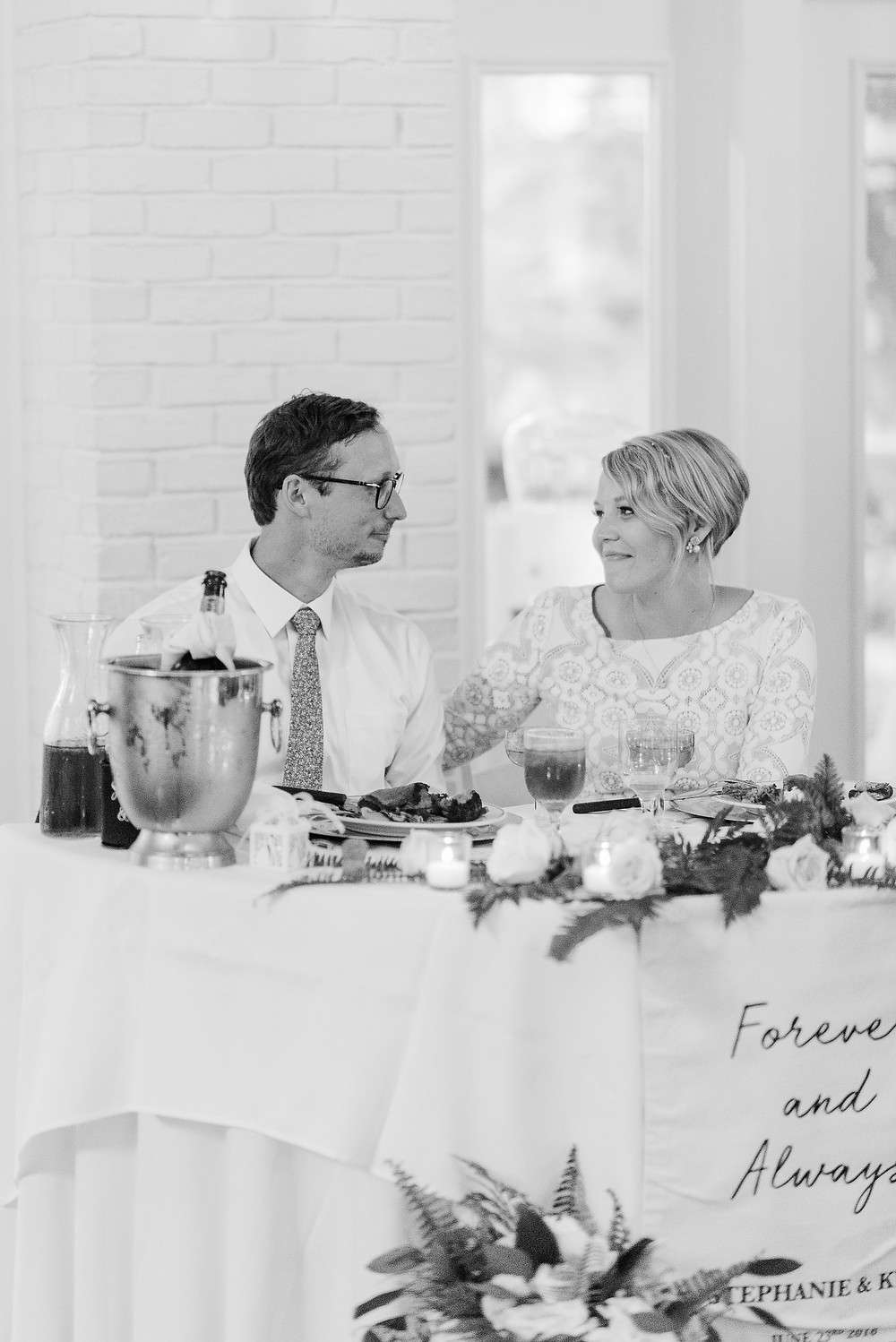 Bride and Groom smiling at each other at their sweetheart table at Sweetwater Branch Inn in Gainesville, Florida.