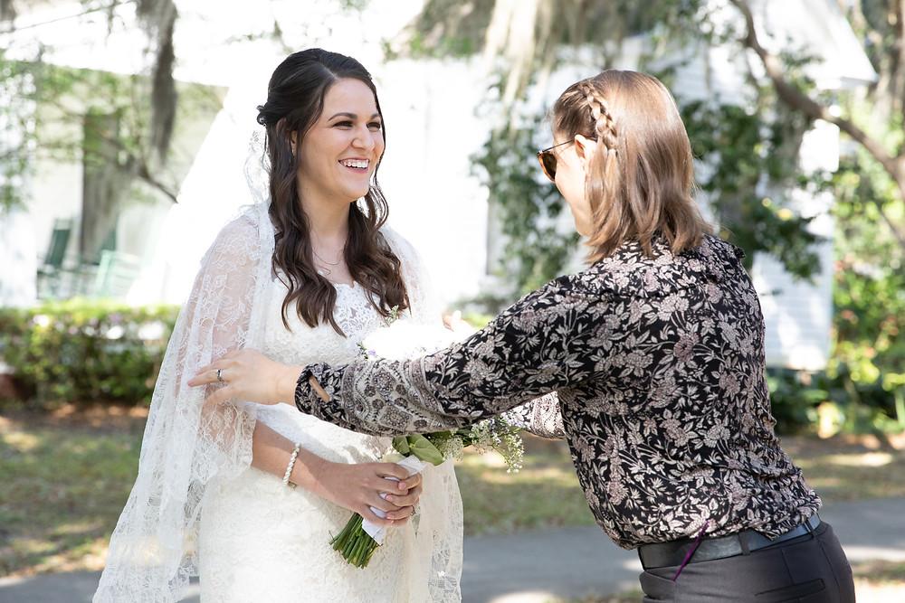 Rachel with MasterPiece Weddings adjusting a bride's veil.