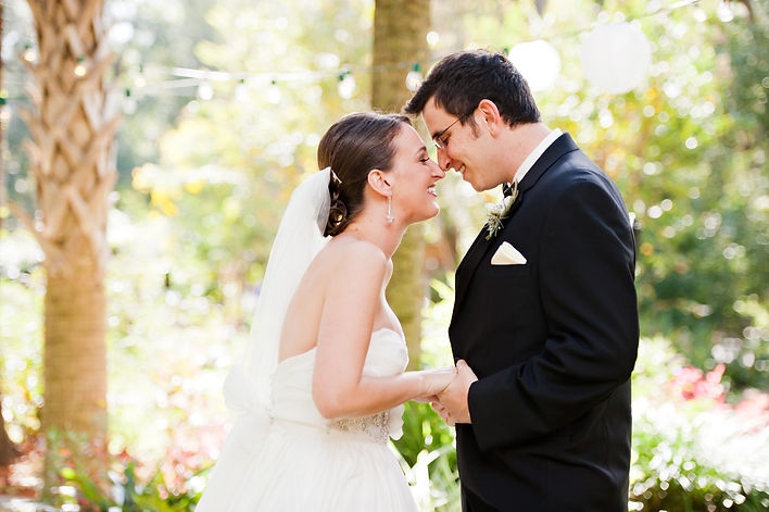 Bride and groom touching foreheads on their wedding day and smiling together.