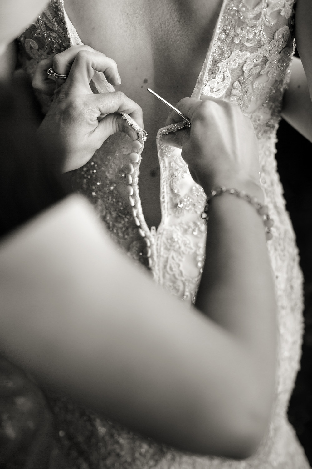 Rachel from MasterPiece Weddings buttoning up a bridal gown for a bride on her wedding day.