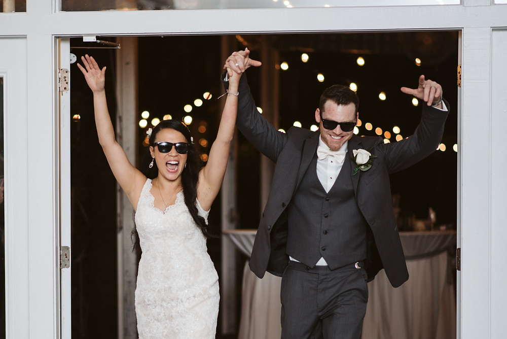 Bride and Groom in sunglasses celebrating as they are announced into their wedding reception.