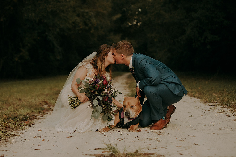 Bride and Groom knelt down over their dog, kissing.