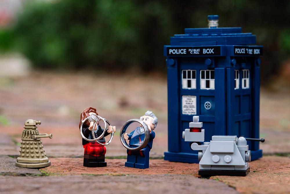 Dr. Who mini figure Legos holding wedding rings next to a Lego Tardis.