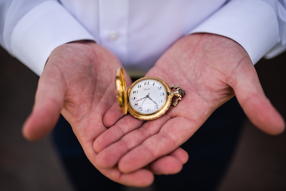 Groom holding a gold pocket watch.