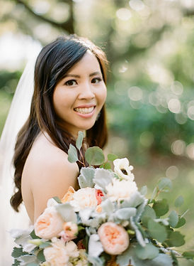 A bride smiles at the camera with her bridal bouquet.