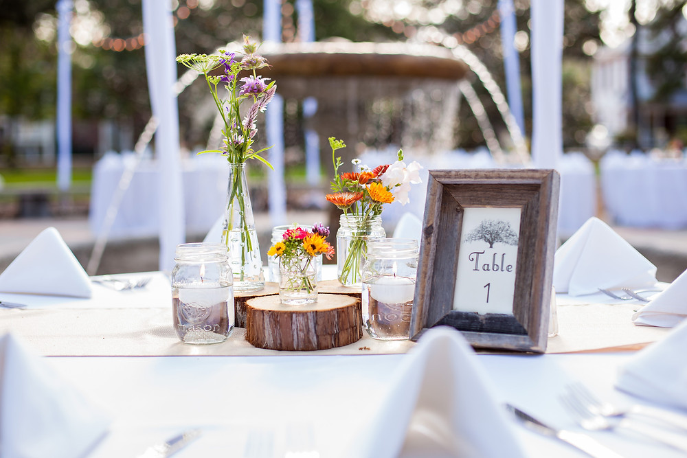 Wedding table setting outside at the Historic Thomas Center in Gainesville, Florida with tree stump accents and Table number.