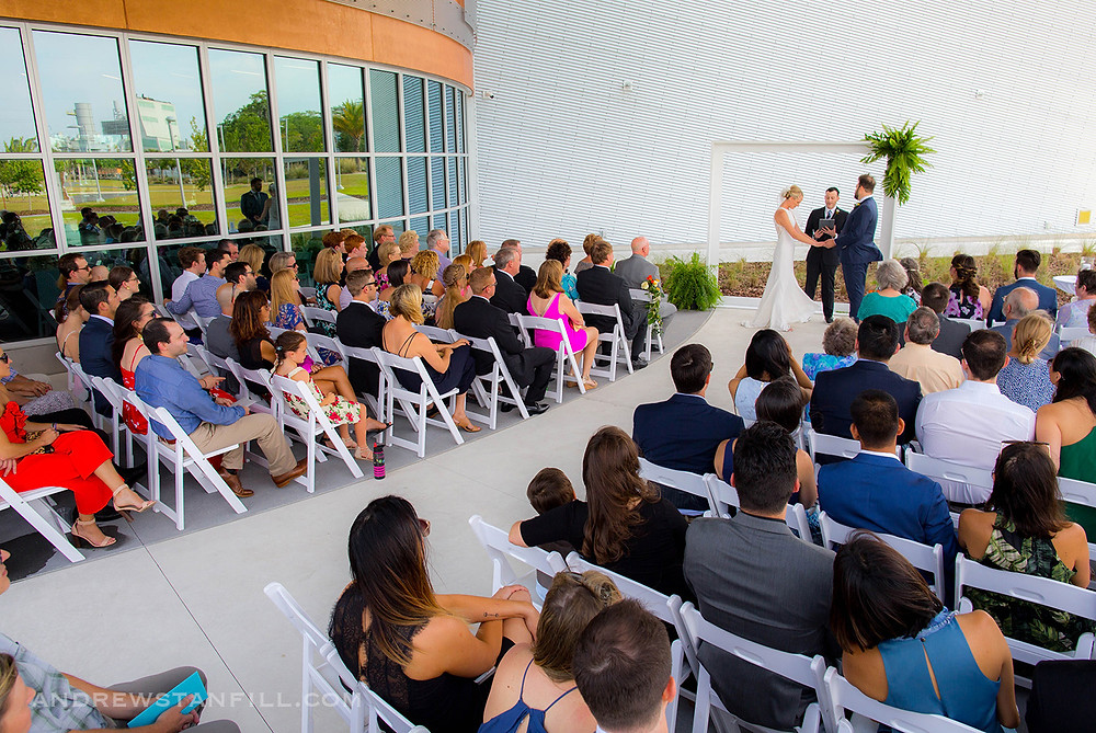Wedding ceremony with bride and groom holding hands on the patio at the Cade Museum in Gainesville, Florida