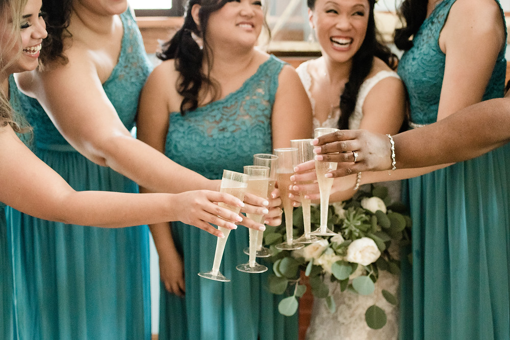 Bride with her bridesmaids toasting with champagne