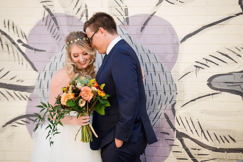 Bride and Groom with bouquet in front of a graffiti art wall