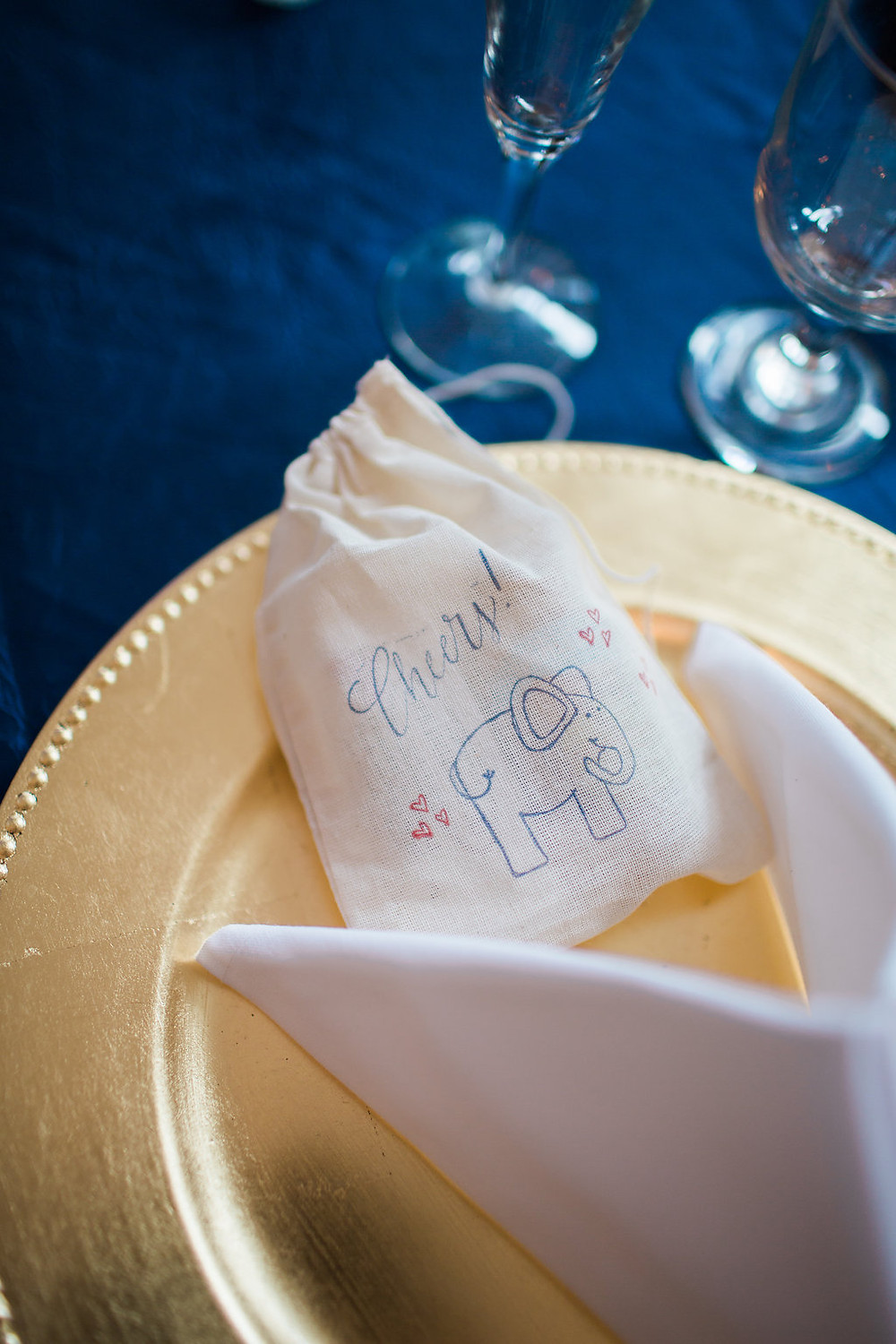 "Wedding place setting with gold charger on a navy blue tablecloth with a ""Cheers"" favor bag"