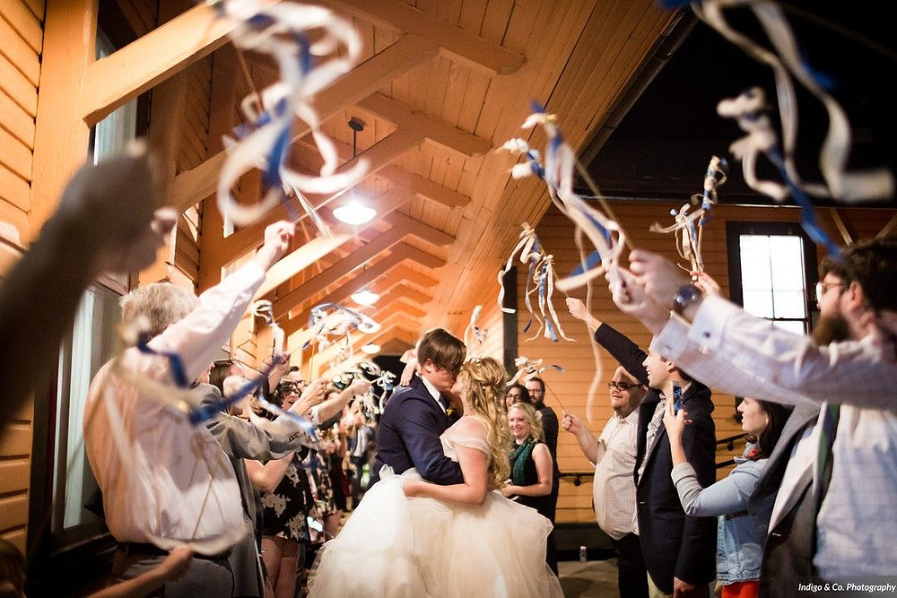 Bride & Groom kissing during a ribbon wand exit