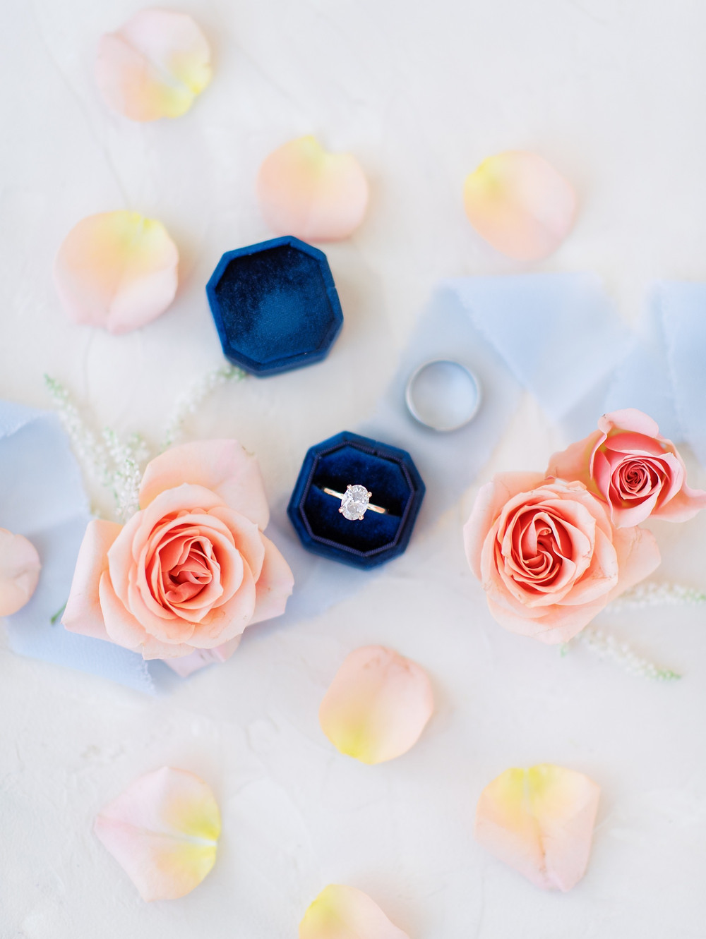 Ring shot of an engagement ring in a blue box with pink roses.