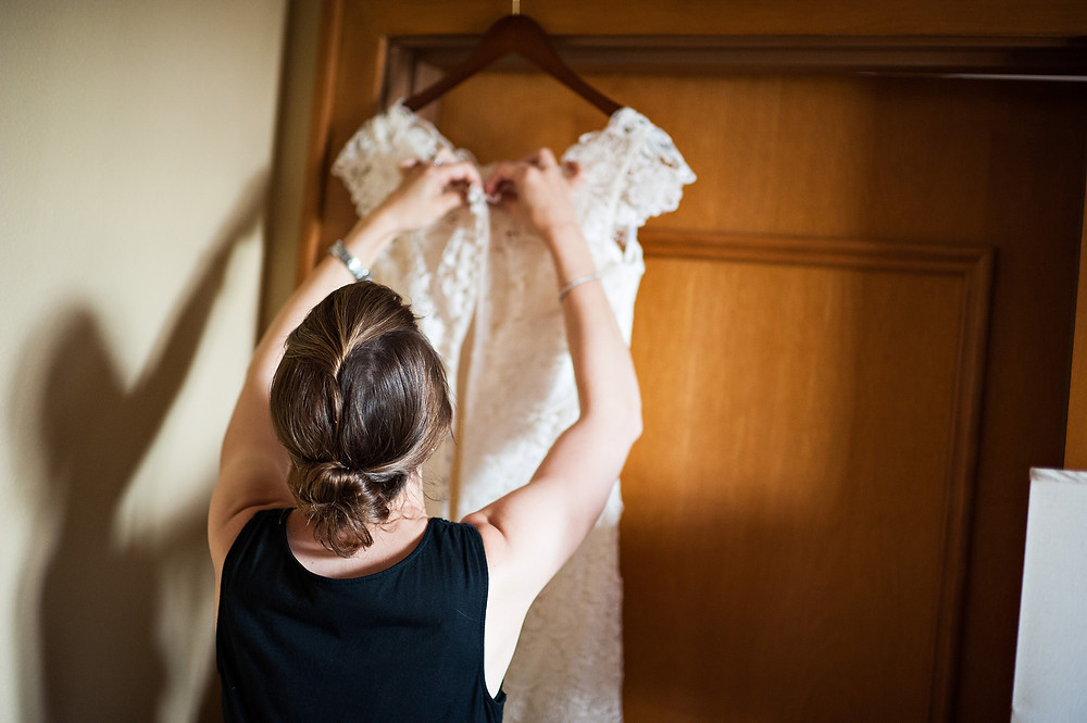 Wedding planner, Rachel Griffin with MasterPiece Weddings, adjusts a bridal gown.