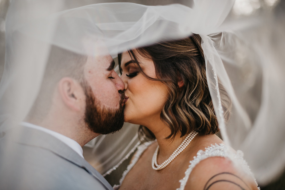 Bride and Groom kissing under her veil on their wedding day at West Light Farm.