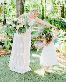 A bride twirls her small flower girl around in gardens, holding her bridal bouquet.