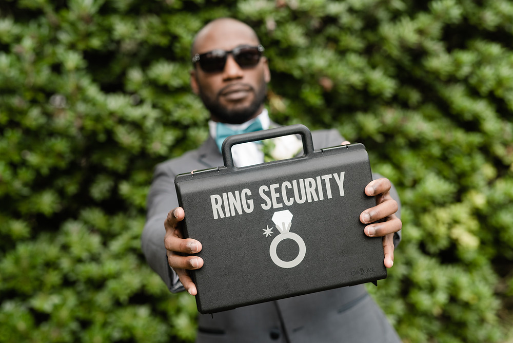 Best Man holding out a Ring Security briefcase.