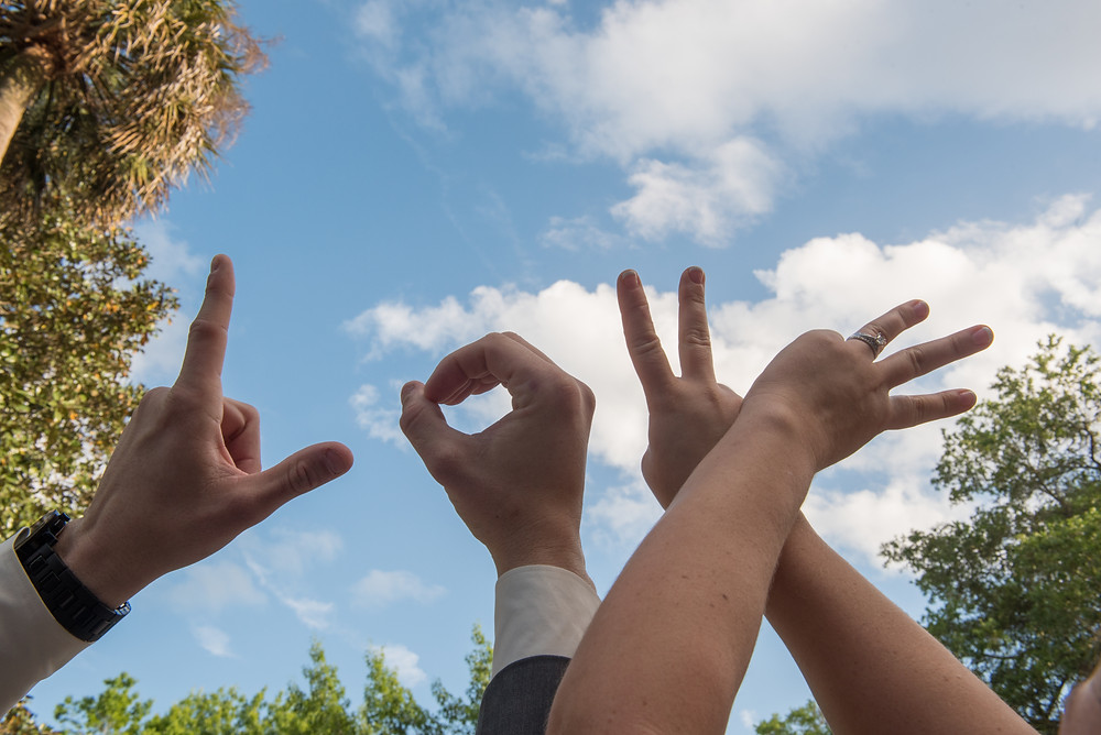 """Fingers spelling out """"Love"""" in the clouds."""