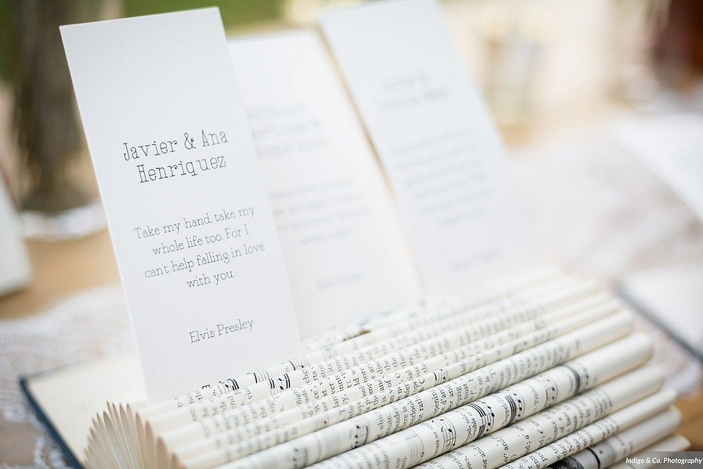 Escort cards tucked in a music book with an Elvis Presley lyric about love.