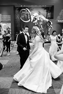 Bride and groom smiling and dancing together at their reception in front of a Wooly Mammoth.