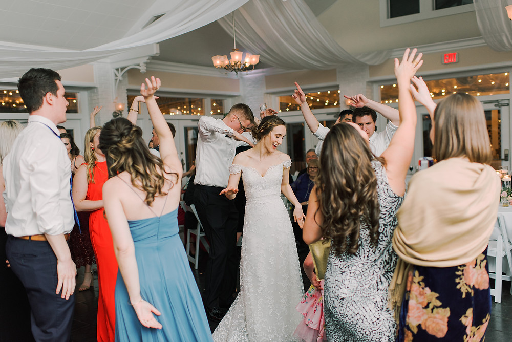 Bride and groom dancing on the dance floor, surrounded by their guests.