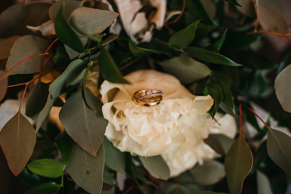 Gold wedding rings nestled on a white rose in a bouquet.