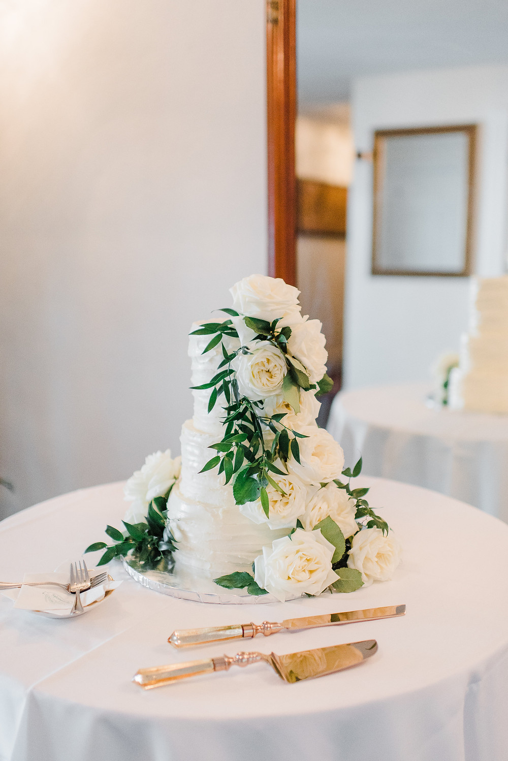 White wedding cake with roses displayed all along the tiers.