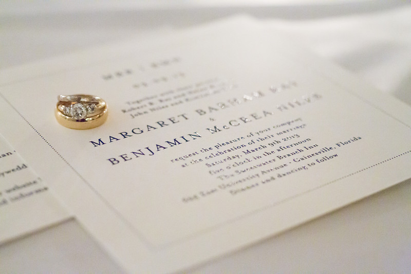 Gold wedding rings on top of a wedding invitation