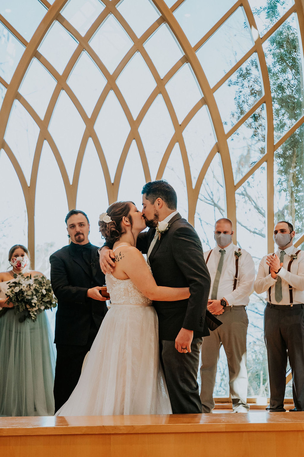 Bride & Groom's first kiss in front of the architectural arched windows of the Baughman Center in Gainesville, Florida during their wedding ceremony.