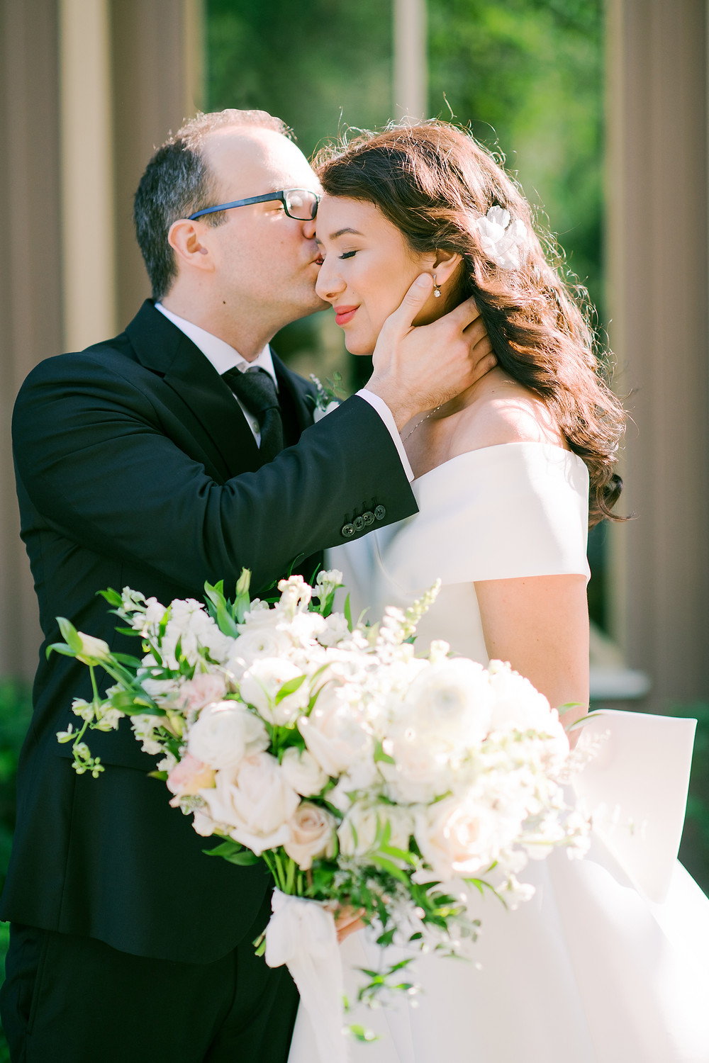 Groom kissing his bride's cheek in front of the Baughman Center in Gainesville, Florida on their wedding day during a first look.
