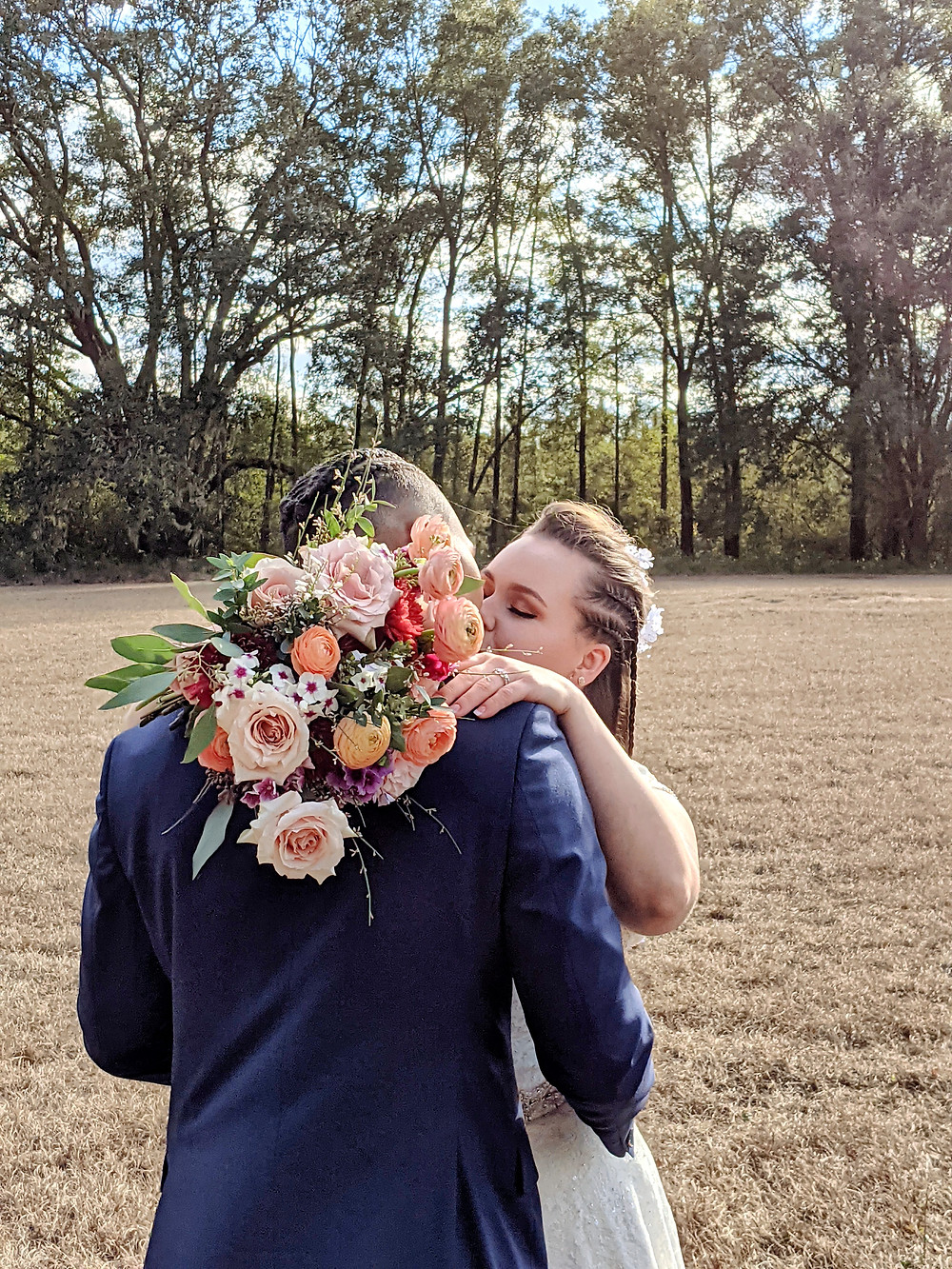Bride kisses her groom with her bouquet at West Light Farm in High Springs, Florida