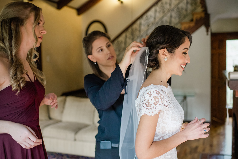 Wedding planner, Rachel Griffin, with MasterPiece Weddings and Events adjust a veil on her bride while a bridesmaid watches.