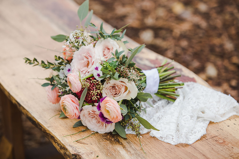 Pink wedding bouquet with a lace handkerchief laying on a wooden bench at West Light Farm.