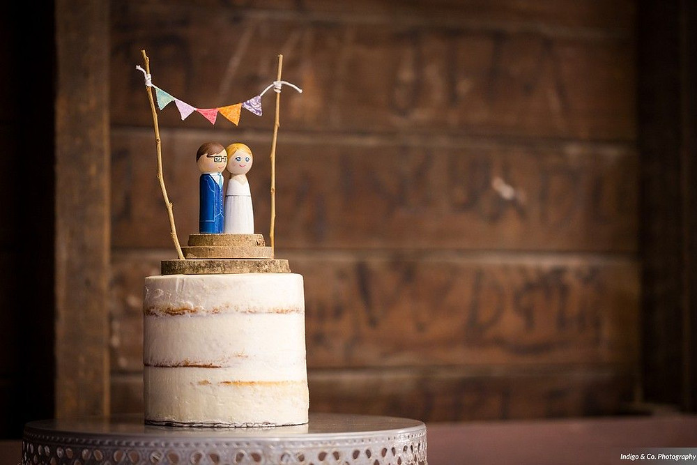 Handmade wedding cake topper of a painted, wooden bride & groom with a colorful triangle banner above them.